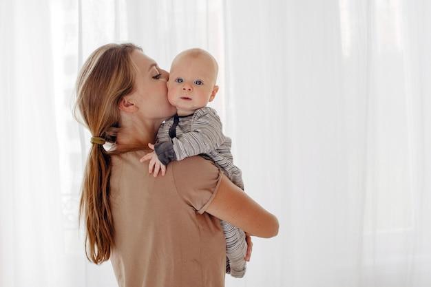 母は彼女の赤ちゃんにキスして抱き締める