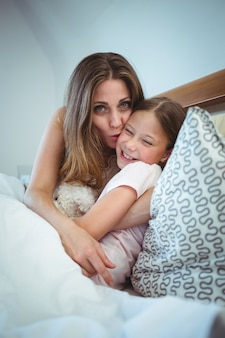 Mother kissing daughter on bed