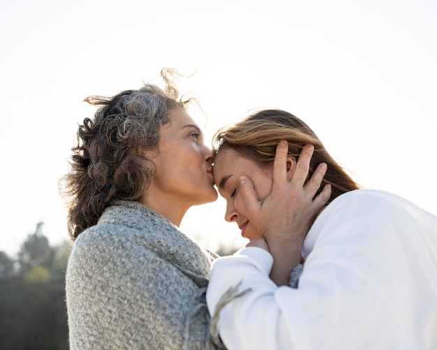 Mother kissing daughter on the forehead outdoors