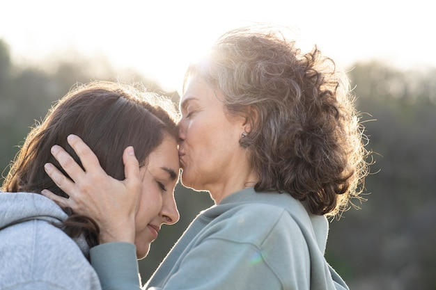 Mother kissing daughter's forehead outdoors