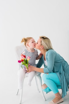 Mother kissing daughter with flowers