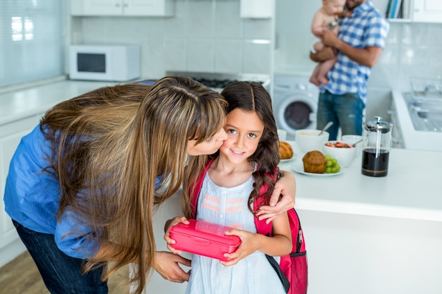 Mother kissing girl holding school lunch box