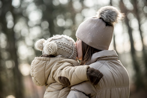 田舎で屋外で子供にキスをする母親
