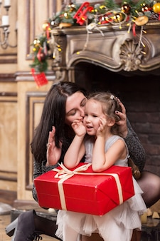 Mother kissing her cute little girl with christmas gift near a fireplace with decorations
