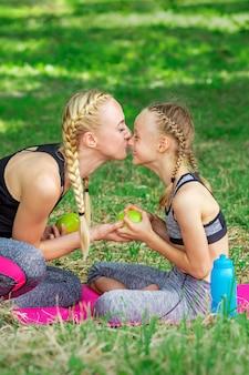 Мать целует дочь в парке