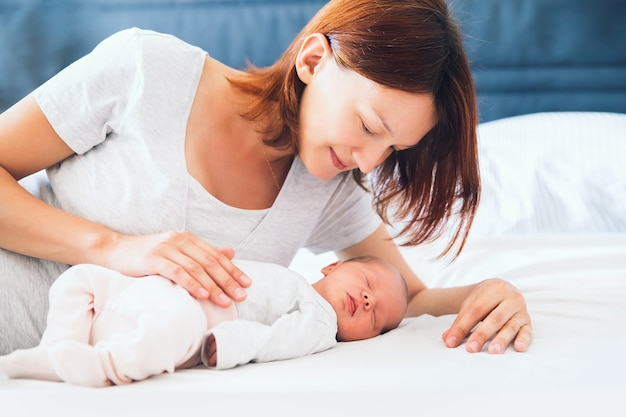 Мать целует своего новорожденного ребенка молодая красивая мама лежит в постели с милым маленьким спящим ребенком