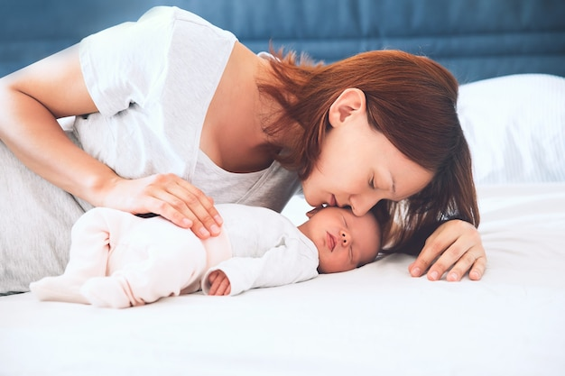 Mother kissing her newborn baby. young beautiful mom lying at bed with a cute little sleeping child. new born baby's first days of life in family at home. loving mother looks at asleep infant.