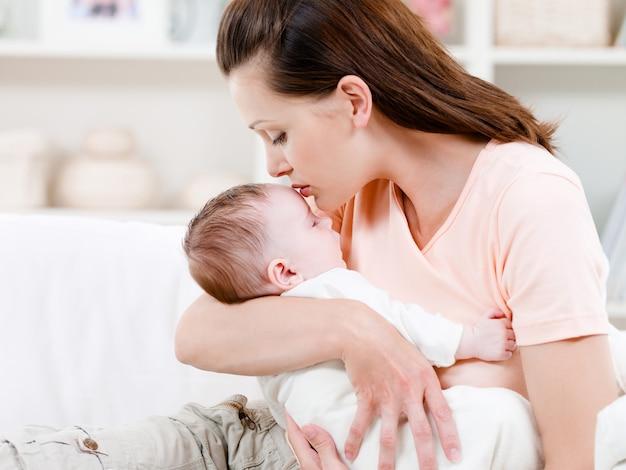母親が眠っている赤ちゃんにキス