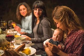 Mother kissing little baby at family dinner