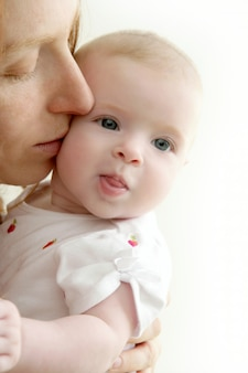 Mother kissing little baby smiling