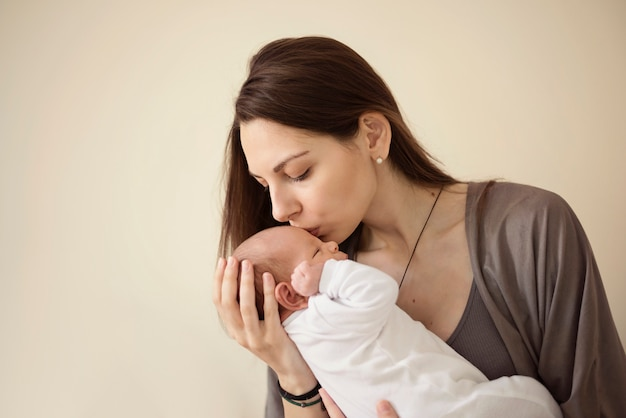Mother kissing newborn son at grey background. portrait of woman and little baby love