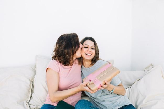 Мать целует женщину за подарок