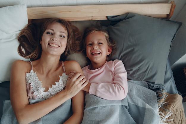 母は小さな娘と一緒にベッドに横になって笑っています。家にいる。コロナウイルスの危険、
