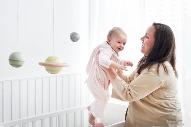 ベビーベッドから赤ちゃんを持ち上げる母親