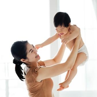 그녀의 귀여운 아기를 들어 올리는 어머니