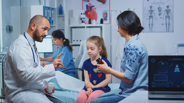 病室に座っている新しい治療のための母親のリスニングドクター。内閣で医療サービスx線治療検査を提供する医学の医療従事者医師の専門家