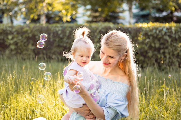 Mother and little baby daughter blowing soap bubbles outdoor at spring day