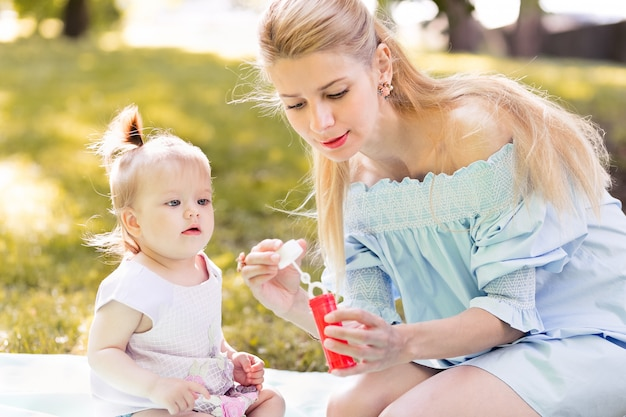 Mother and little baby daughter blowing soap bubbles outdoor