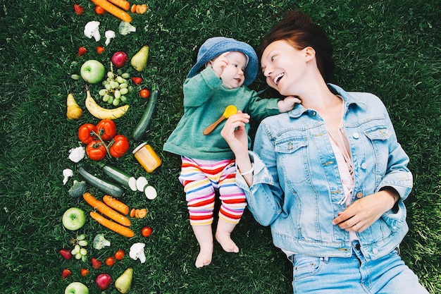 Mother and little baby on green grass with frame of  fresh fruits and vegetableshealthy nutrition