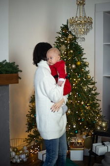 Mother and little baby in santa hats at home