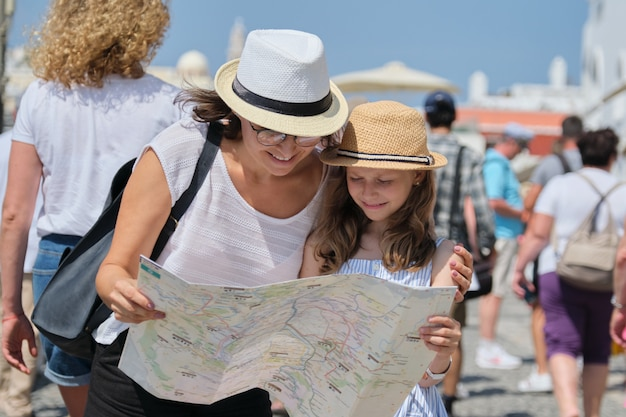 Mother and little child daughter traveling, reading map