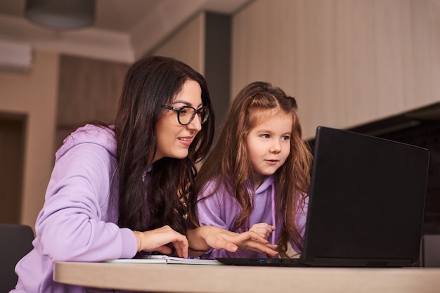 Mother and little daughter doing homework online distance learning online education