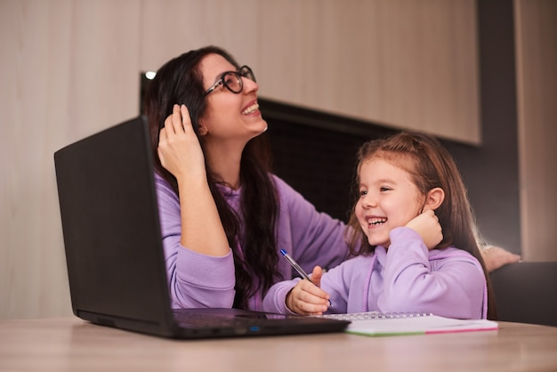 Mother and little daughter doing homework online at home together