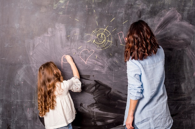Mother and little daughter drawing on blackboard