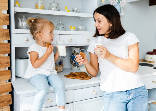 Mother and little daughter drinking milk