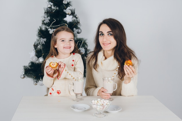 Mother and little daughter eat the delicious cupcakes