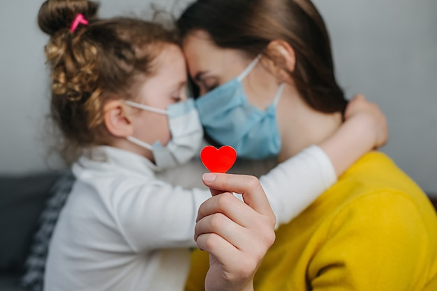Mother and little daughter embrace bonding, wearing facial medical mask, holding red heart a way to show appreciation and to thank all essential employees during covid-19 pandemic. selective focus