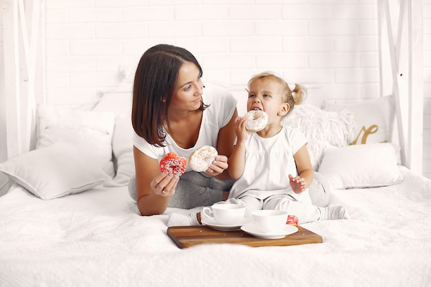Mother and little daughter have a breakfast at home