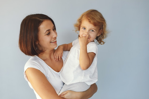 Mother and little daughter have fun on a blue background
