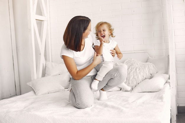 Mother and little daughter have fun at home