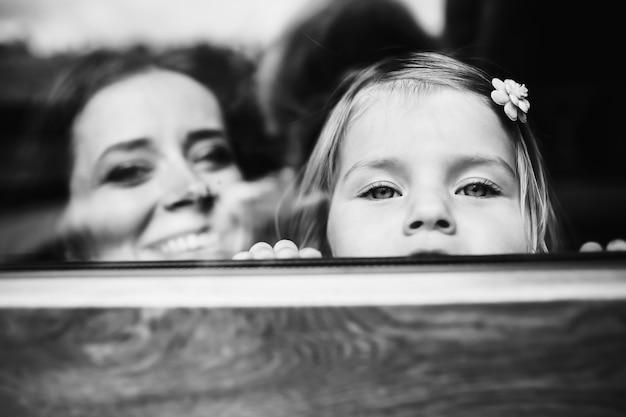 Madre e figlia piccola guardano oltre il davanzale della finestra