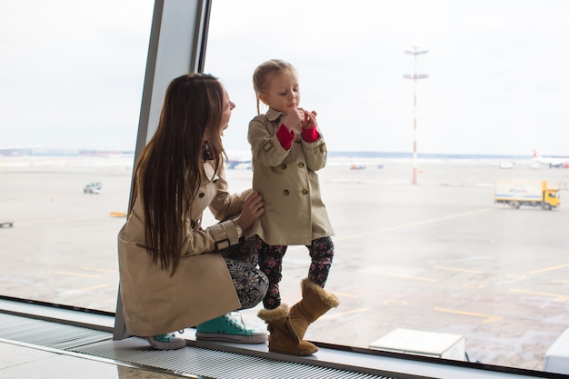 Mother and little daughter looking out the window at airport terminal
