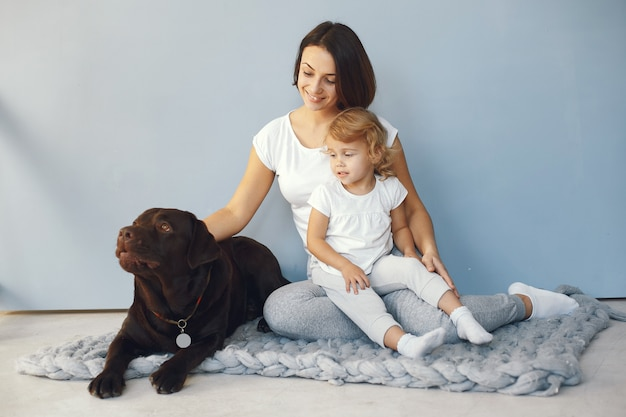 Mother and little daughter playing with dog at home