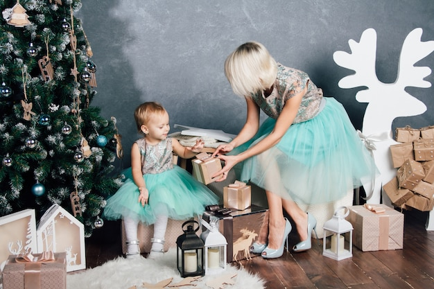 Mother and little daughter posing in the new year interior