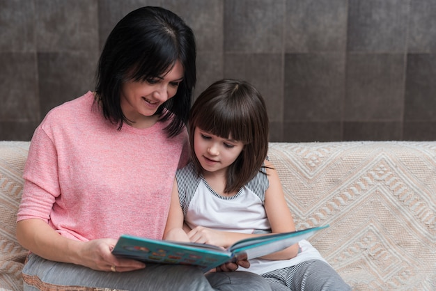 Mother and little daughter reading book on couch