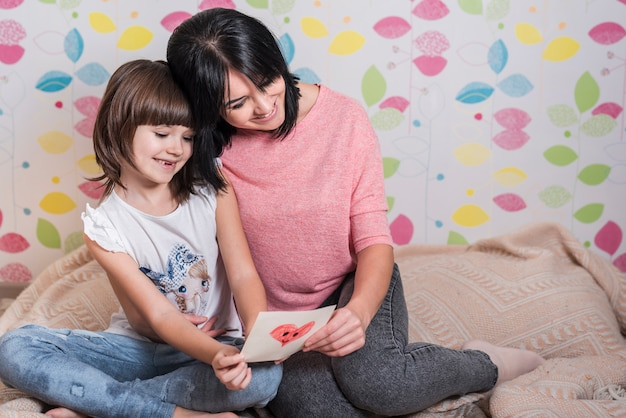 Mother and little daughter reading greeting card
