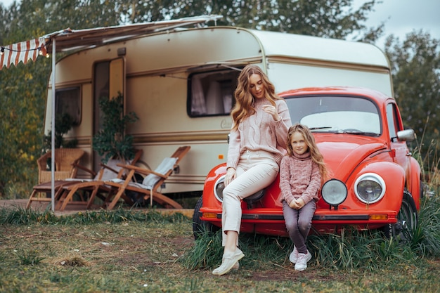 Mother and little daughter relaxing and having fun in countryside on camper van vacation with red retro car