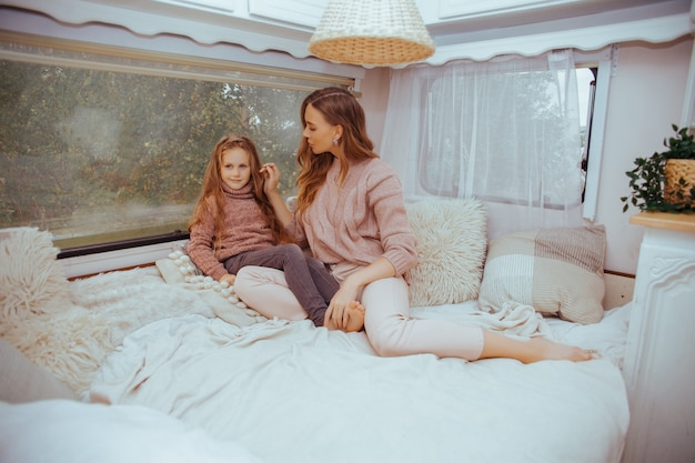 Mother and little daughter relaxing and having fun in countryside inside camper van