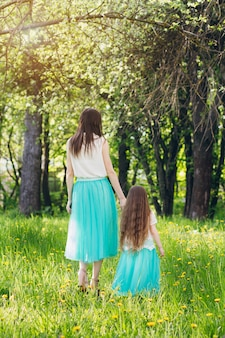 Mother and a little daughter walk in the spring blooming apple