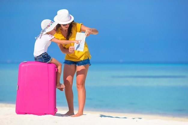 Mother and little daughter with luggage and map on beach