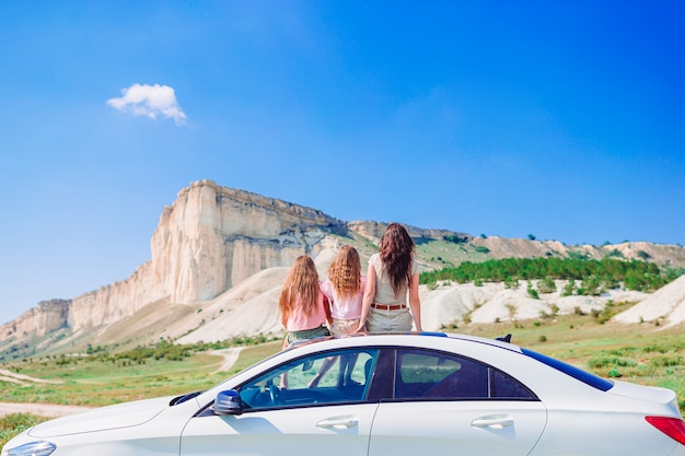 Mother and little daughters on summer car vacation