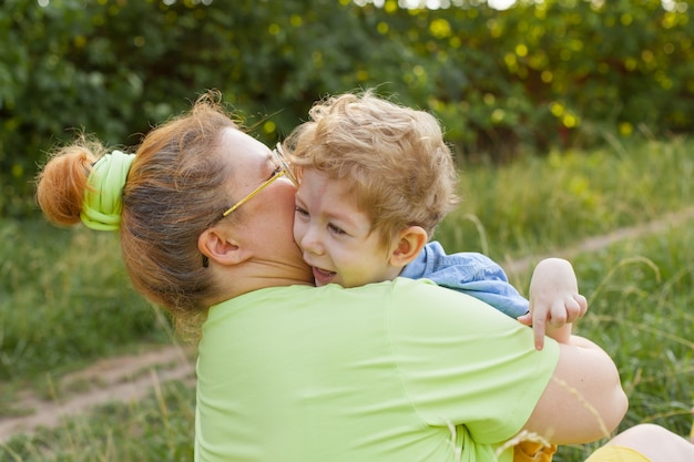 A mother and a little disabled boy hug and play in nature. disability. infantile paralysis. mother's love. happy childhood.