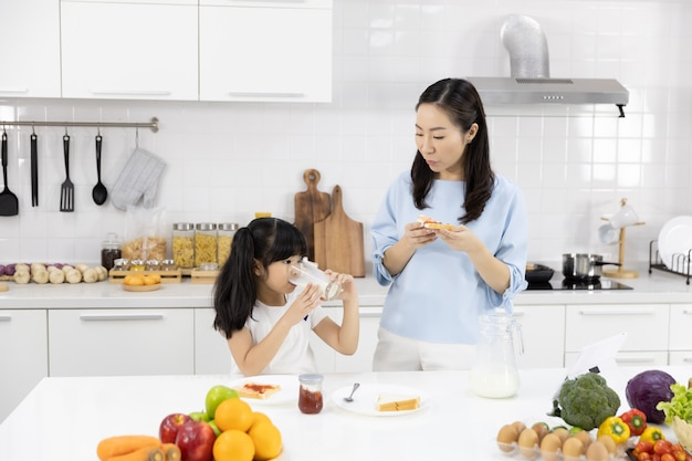 Mother and little girl are eating breakfast in the kitchen at home