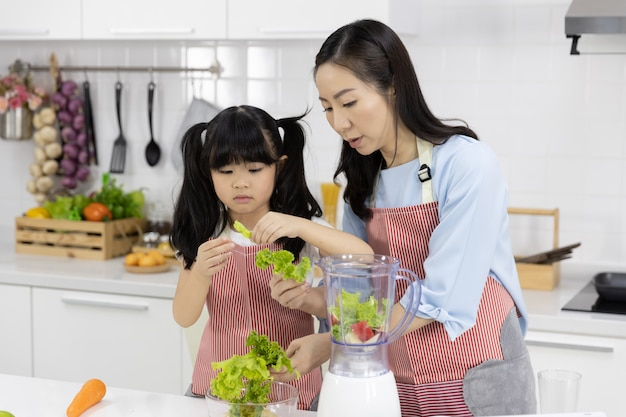 Mother and little girl are preparing the salad in a bowl