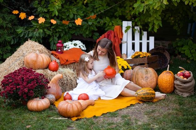 Mother and little girl holding a pumpkin