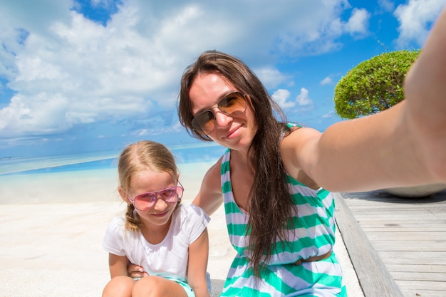 Mother and little girl taking selfie at tropical beach